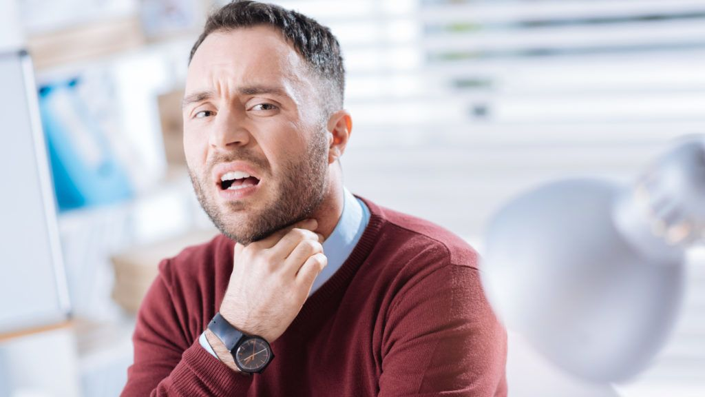 Sore throat. Young bearded worker sitting in his light big office and touching his neck while having an awful sore throat