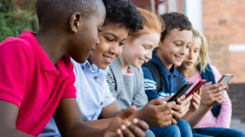 Pupils using mobile phone at the elementary school during recreation time. Group of multiethnic children sitting in a row and typing a message on smartphone. Young boys and girls playing with cellphone.