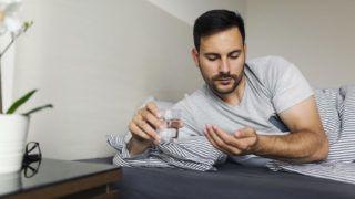 Man having morning migraine and taking medication pills