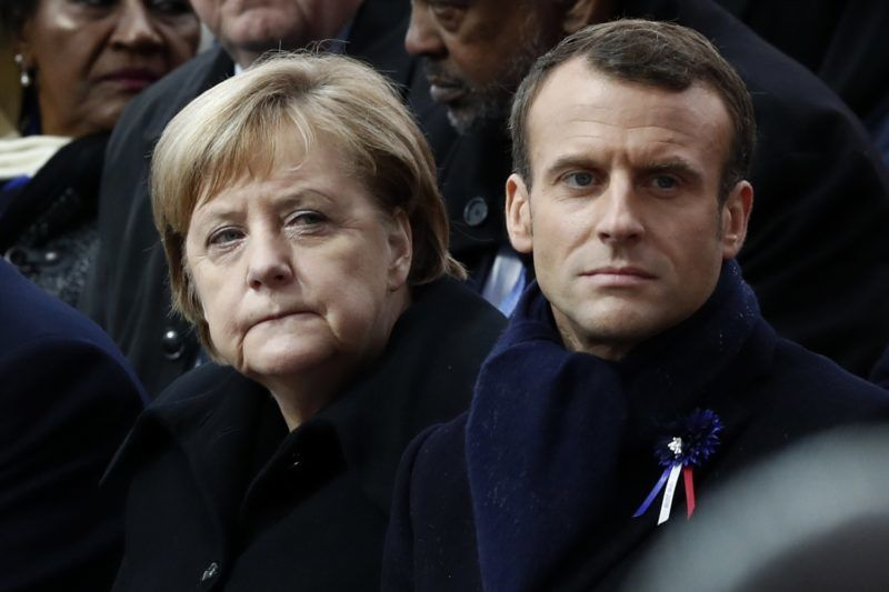German Chancellor Angela Merkel (L) and French President Emmanuel Macron attend a ceremony at the Arc de Triomphe in Paris on November 11, 2018 as part of commemorations marking the 100th anniversary of the 11 November 1918 armistice, ending World War I. (Photo by BENOIT TESSIER / POOL / AFP)