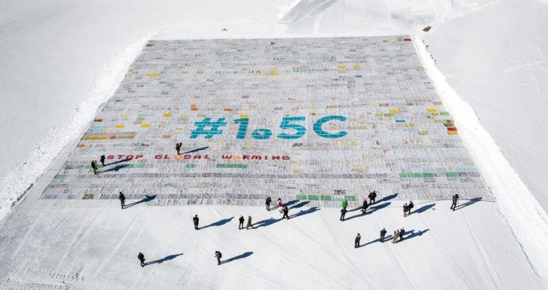 """An aerial view shows a massive collage of 125,000 drawings and messages from children from around the world about climate change seen rolled out on the Aletsch Glacier at an altitude of 3,400 metres near the Jungfraujoch in the Swiss Alps smashing the world record for the giant postcard, on November 16, 2018. - The mosaic of postcards, measuring 2,500 square metres (26,910 square feet), was laid out in the snow to """"boost a global youth climate movement ahead of the next global climate conference (COP24) in Poland"""", next month, said the WAVE foundation, which organised the event in cooperation with Swiss authorities. (Photo by Fabrice COFFRINI / AFP)"""