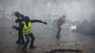 Yellow vests (Gilets jaunes) protestors clash with riot police amid tear gas during a demonstration on the Champs Elysees in Paris, on November 24, 2018 during a protest against rising oil prices and living costs. - Demonstrators who have blocked French roads over the past week dressed in high-visibility jackets, are set to cause another day of disruption on November 24 amid calls to bring Paris to a standstill. (Photo by Lucas BARIOULET / AFP)