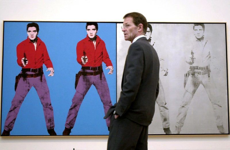Tate Modern director Nicholas Serota standsin front of a work featuring Elvis Presely by the enigmatic American artist Andy Warhol at the Tate Modern in London 05 February 2002.  A major retrospective of the controversial Warhol's work is expected to be a highlight of the English capital's cultural year. AFP PHOTO/Nicolas ASFOURI (Photo by NICOLAS ASFOURI / AFP)