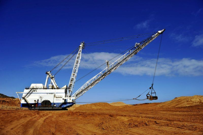 In this picture taken on August 12, 2009 a De Beers earth moving industrial is engaged in filling in a former Diamond mine shaft on one of the De Beers restoration site on the Northern Cape coastline on the outskirt of the diamonds giant De Beers owned mining town of Kleinzee, South Africa. Isolated under strict security for the 80 years diamonds have been mined there, this part of the area nicknamed the Diamond Coast hangs in limbo as De Beers embarks on one of the most ambitious mining restoration projects to date. Since 2007 the world's leading diamond company has drastically reduced operations at the mine as the precious gem runs out, reducing staff from about 3,000 to 250. Situated some 600km (370 miles) north of Cape Town in the country's biggest and most sparsely populated provinces, the Northern Cape mining town Kleinzee is barely clinging to life. AFP PHOTO/GIANLUIGI GUERCIA (Photo by GIANLUIGI GUERCIA / AFP)