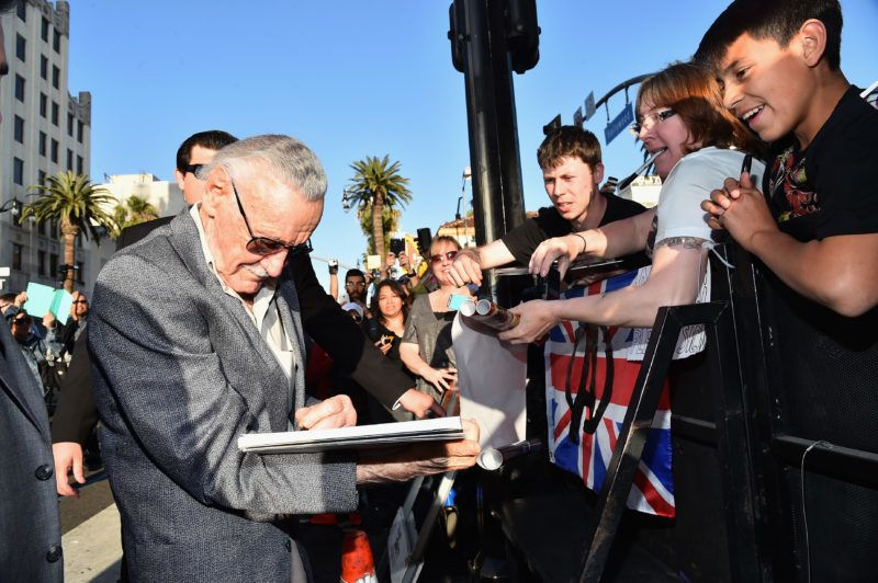 """HOLLYWOOD, CA - APRIL 13: executive producer Stan Lee (L) signs autographs for fans at the world premiere of Marvel's """"Avengers: Age Of Ultron"""" at the Dolby Theatre on April 13, 2015 in Hollywood, California.   Alberto E. Rodriguez/Getty Images for Disney/AFP"""