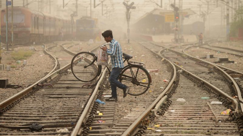 """An Indian commuter crosses railway tracks as dust covers sky in Jalandhar on June 15, 2018. - Air pollution soared in New Delhi on June 14 to hazardous levels rarely seen outside winter months as sand blown from deserts enveloped the Indian capital in a once-in-a-decade phenomenon. Doctors warned the visible grit carried by hot summer winds posed serious health risks to the city of 20 million and there was little to do """"but pray for rain"""". (Photo by Shammi MEHRA / AFP)"""