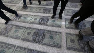 Iranian protesters trample on huge prints of US 100 dollar banknote images during a demonstration outside the former US embassy in the capital Tehran on November 4, 2018, to mark the anniversary of its storming by student protesters that triggered a hostage crisis in 1979. - Thousands joined rallies in Tehran and other Iranian cities, carrying placards that mocked President Donald Trump, wiping their feet on fake dollar bills, and engaging in the usual ritual of burning the US flag. (Photo by ATTA KENARE / AFP)