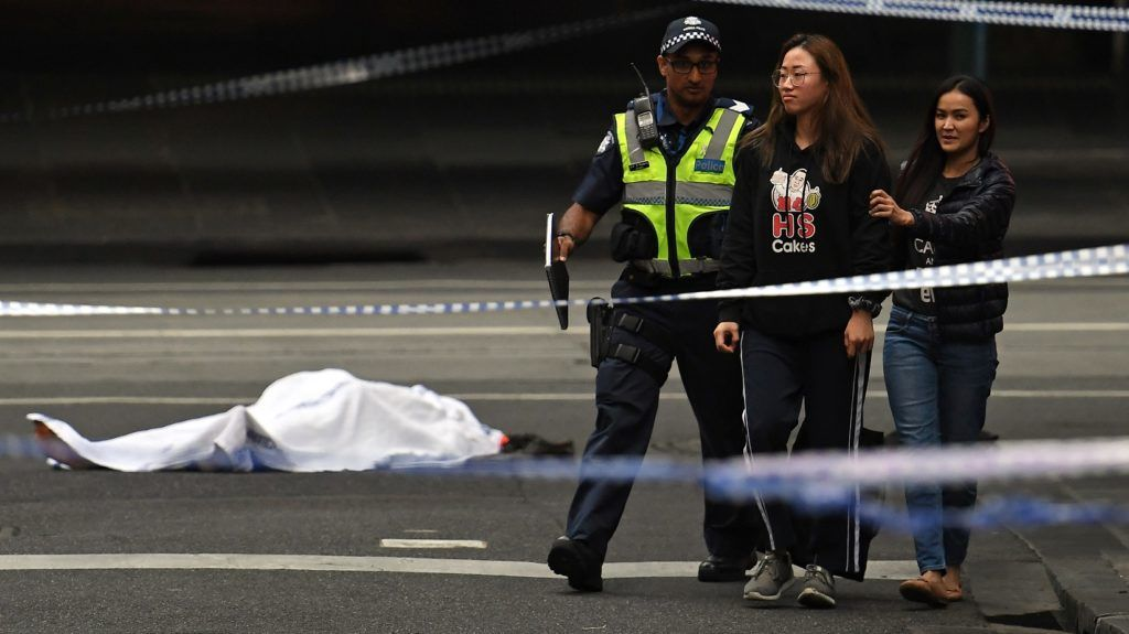 A police officer directs people away from the crime scene as a body is seen covered with a white sheet following a stabbing incident in Melbourne on November 9, 2018. - One person was killed and multiple people hurt in a rush hour stabbing incident in Melbourne's central business district, police said on November 9, after they apprehended a suspect near a burning vehicle. (Photo by WILLIAM WEST / AFP)