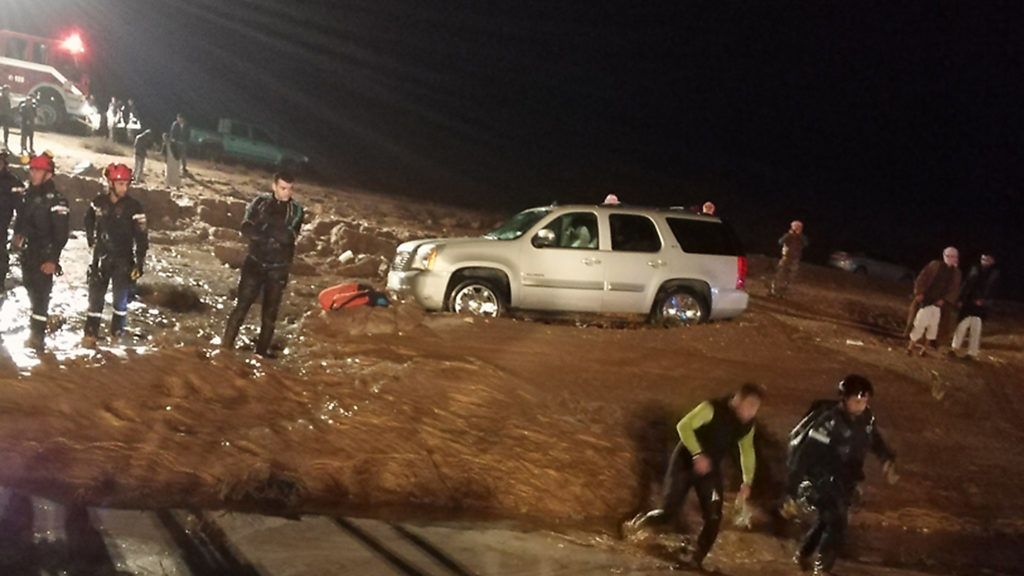 A handout picture released by the official Jordanian news agency, PETRA on November 9, 2018, shows rescuers at the scene of a flood in the JOrdanian city of Madaba near the capital Jordan. - Flash floods killed 11 people in Jordan and forced nearly 4,000 tourists to flee the famed ancient desert city of Petra, emergency services said. According to the same source, one person was reported killed in Maan. (Photo by Handout / various sources / AFP)