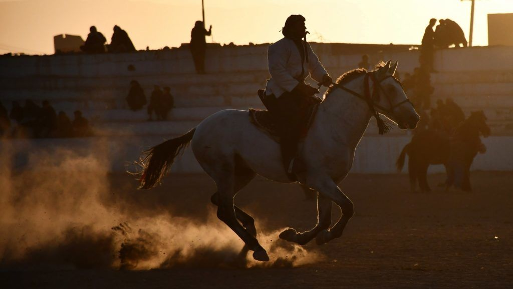 In this photograph taken on November 23, 2018, Afghan horsemen compete during a game of the traditional sport of Buzkashi, in Mazar-i-Sharif. - The ancient game of Buzkashi is an Afghan national sport which is played between two teams of horsemen competing to throw a animal carcass into a circle. (Photo by FARSHAD USYAN / AFP)