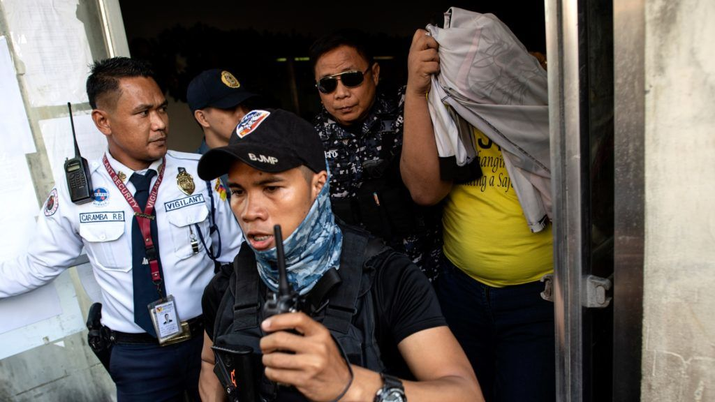 A policeman (wearing yellow shirt), who was involved in the killing of Kian delos Santos in 2017, is escorted out of the Caloocan Regional Trial court in Manila on November 29, 2018. - Three Philippine policemen were sentenced on November 29 to decades in prison for murdering a teenager during an anti-narcotics sweep, a first conviction of officers carrying out President Rodrigo Duterte's war on drugs. Duterte has vowed to pardon authorities involved in his bloody crackdown, but even he refused to defend the 2017 killing of Kian delos Santos in a dank Manila alley -- which helped spark rare protests against the campaign. (Photo by Noel CELIS / AFP)