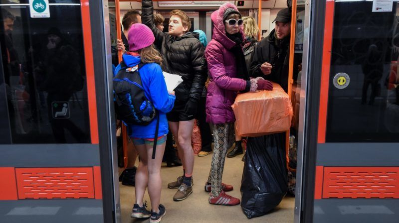 """Passengers without pants stand in a subway train during the """"No Pants Subway Ride"""" on January 7, 2018 in Prague. - The No Pants Subway Ride is an annual event which was started in 2002 by Improv Everywhere in New York, the goal is for riders to get on the subway train dressed in normal winter clothes without pants and stay serious. (Photo by Michal CIZEK / AFP)"""