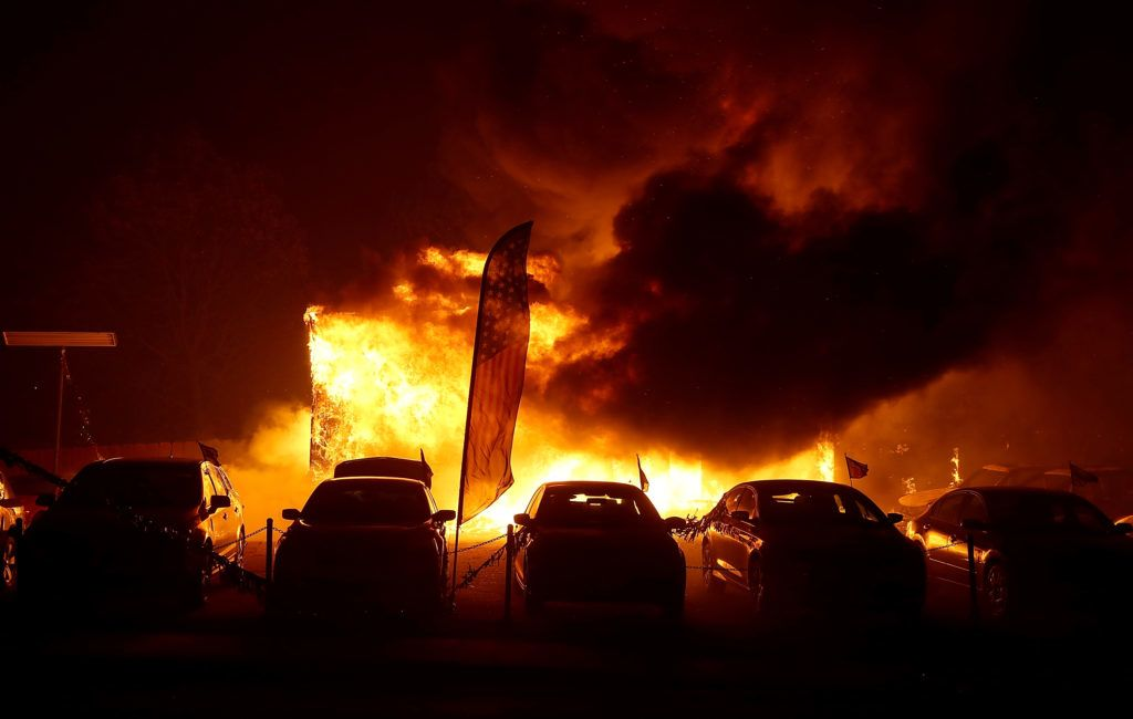 PARADISE, CA - NOVEMBER 08: A car dealership burns as the Camp Fire moves through the area on November 8, 2018 in Paradise, California. Fueled by high winds and low humidity, the rapidly spreading wildfire has ripped through the town of Paradise, charring 18,000 acres and destroying dozens of homes in a matter of hours. The fire is currently at zero containment.   Justin Sullivan/Getty Images/AFP