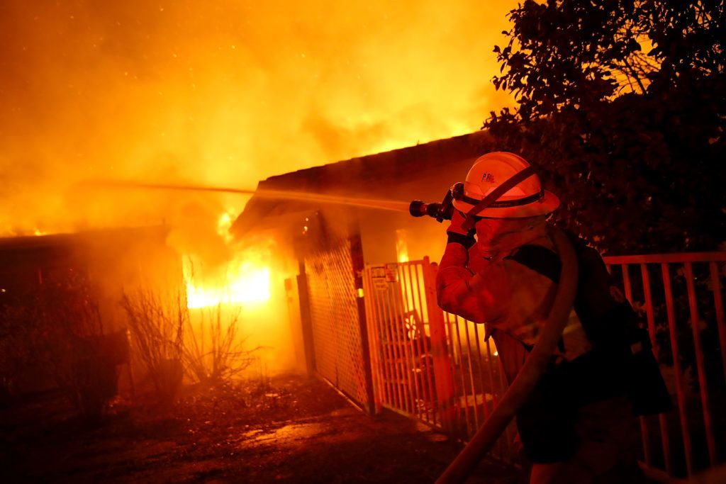 PARADISE, CA - NOVEMBER 08: Firefighters try to contain a fire so it doesn't spread to a neighboring building as the Camp Fire moves through the area on November 8, 2018 in Paradise, California. Fueled by high winds and low humidity, the rapidly spreading wildfire has ripped through the town of Paradise, charring 18,000 acres and destroying dozens of homes in a matter of hours. The fire is currently at zero containment.   Justin Sullivan/Getty Images/AFP