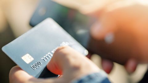 A man uses a mobile phone to pay for utilities. Concepts of using mobile technologies and smarfon in mobile applications in the online business for payment with a credit card remotely
