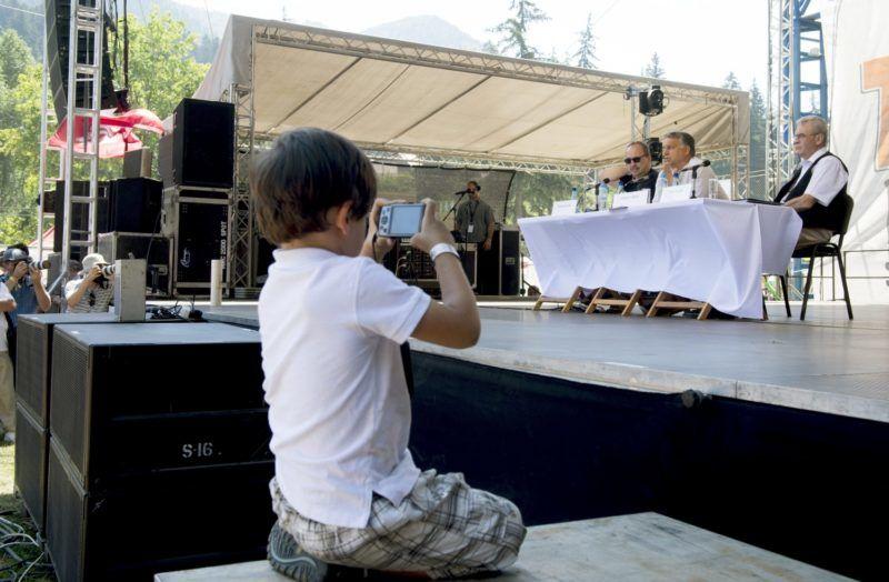 Tusnádfürdõ, 2015. július 25. Egy kisfiú fényképezi, amint Orbán Viktor miniszterelnök beszédet mond a 26. Bálványosi Nyári Szabadegyetem és Diáktáborban (Tusványos) az erdélyi Tusnádfürdõn 2015. július 25-én. A kormányfõ mellett Németh Zsolt, az Országgyûlés külügyi bizottságának fideszes elnöke (b) és Tõkés László református lelkész, európai parlamenti képviselõ, az Erdélyi Magyar Nemzeti Tanács (EMNT) elnöke. MTI Fotó: Koszticsák Szilárd