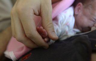 Budapest, 2014. szeptember 8. Egy férfi fogja gyermeke kezét a Magyar Honvédség Egészségügyi Központ (MH EK) koraszülött intenzív centrumában (PIC) Budapesten 2014. szeptember 8-án. Átadták az intenzív centrum korszerûsített orvostechnikai eszközparkját. A több mint 112 millió forintos vissza nem térítendõ uniós forrásból megvalósult projekt során a legkorszerûbb inkubátorokat, lélegeztetõ gépeket, multifunkciós betegõrzõ monitorokat, ultrahangkészülékeket vásároltak, illetve megújult az ezeket összekötõ informatikai rendszer is. MTI Fotó: Bruzák Noémi