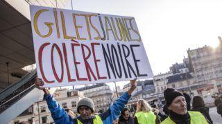 """Párizs, 2018. november 17. Az interneten felháborodott autósok által néhány hete indított, a gépkocsikban kötelezõen tartandó láthatósági sárga mellényrõl elnevezett sárga mellényesek mozgalmának támogatói """"Sárga mellény - fekete harag"""" feliratú transzparenssel tiltakoznak az üzemanyag adójának emelése ellen Párizsban 2018. november 17-én. Franciaországban: mintegy ezer helyen ötvenezren tiltakoztak a civilek által szervezett megmozdulásokon. MTI/EPA/Christophe Petit Tesson"""