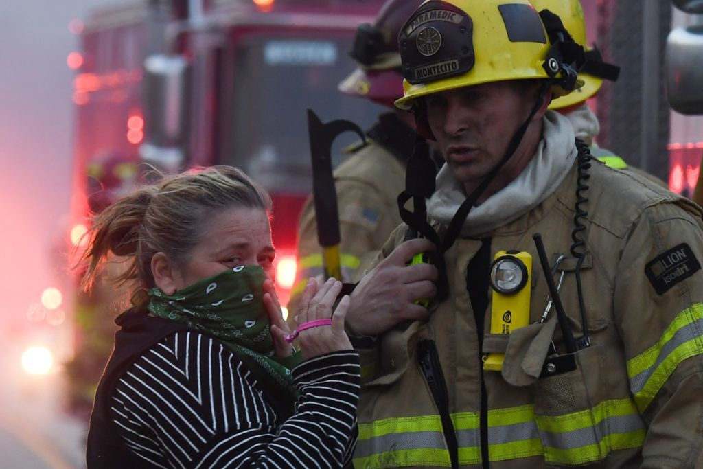 A local resident speaks with firefighters stationed along Pacific Coast Highway (Highway 1) to battle the Woolsey Fire on November 9, 2018 in Malibu, California. - About 75,000 homes have been evacuated in Los Angeles and Ventura counties due to two fires in the region. (Photo by Robyn Beck / AFP)