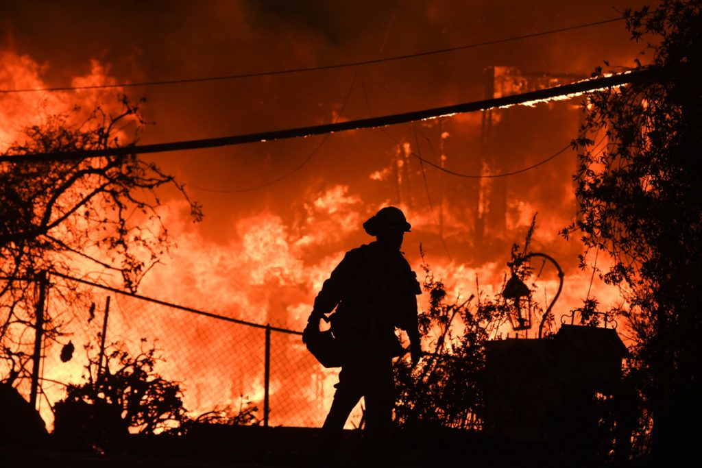 A firefighter is silhouetted by a burning home along Pacific Coast Highway (Highway 1) during the Woolsey Fire on November 9, 2018 in Malibu, California. - About 75,000 homes have been evacuated in Los Angeles and Ventura counties due to two fires in the region. (Photo by Robyn Beck / AFP)