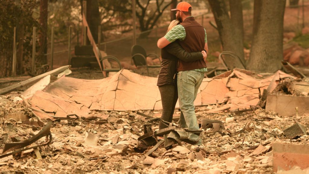 Chris and Nancy Brown embrace while looking over the remains of their burned residence after the Camp fire tore through the region in Paradise, California on November 12, 2018. - Thousands of firefighters spent a fifth day digging battle lines to contain California's worst ever wildfire as the wind-whipped flames cleaved a merciless path through the state's northern hills, leaving death and devastation in their wake. The Camp Fire -- in the foothills of the Sierra Nevada mountains north of Sacramento -- has killed 29 people, matching the state's deadliest ever brush blaze 85 years ago. More than 200 people are still unaccounted for, according to officials. (Photo by Josh Edelson / AFP)