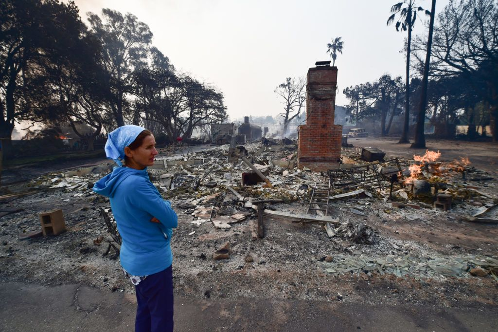 Local resident Lea Johnson views the scene on November 10, 2018 after the Woolsey Fire tore through the Point Dume neighborhood of Malibu, California, overnight, November 10, 2018. - Firefighters in California on Saturday battled raging blazes at both ends of the state that have left at least nine people dead and thousands of homes destroyed, but there was little hope of containing the flames anytime soon. More than 250,000 people have been ordered to evacuate a wide area near the state capital Sacramento and, in southern California, the Hollywood resort town of Malibu. (Photo by Robyn Beck / AFP)