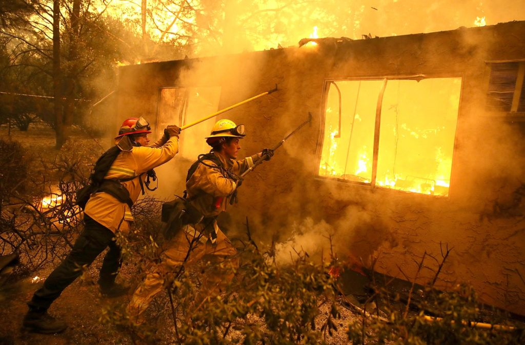 PARADISE, CA - NOVEMBER 09: Firefighters try to keep flames from burning home from spreading to a neighboring apartment complex as they battle the Camp Fire on November 9, 2018 in Paradise, California. Fueled by high winds and low humidity, the rapidly spreading Camp Fire ripped through the town of Paradise and has quickly charred 70,000 acres and has destroyed numerous homes and businesses in a matter of hours. The fire is currently at five percent containment.   Justin Sullivan/Getty Images/AFP