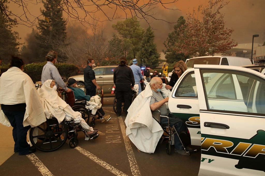 PARADISE, CA - NOVEMBER 08: Hospital workers and first responders evacuate patients from the Feather River Hospital as the Camp Fire moves through the area on November 8, 2018 in Paradise, California. Fueled by high winds and low humidity, the rapidly spreading Camp Fire has ripped through the town of Paradise and has quickly charred 18,000 acres and has destroyed dozens of homes in a matter of hours. The fire is currently at zero containment.   Justin Sullivan/Getty Images/AFP