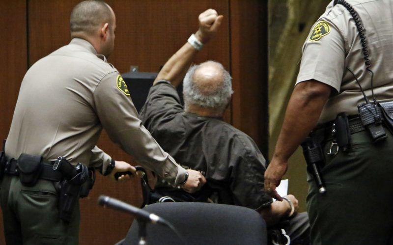 LOS ANGELES, CA  SEPTEMBER 25, 2014 - A defiant convicted serial killer Samuel Little, 74, raises his arm in the air as he is led out of the courtroom as victims and family of victims applauded at the conclusion of the hearing today September 25, 2015 after he was sentenced to life in prison without the possibility of parole for the killings of three women in the Los Angeles area in the 1980s. Prosecutor Beth Silverman called Samuel Little a``remorseless, vicious serial killer'' and said the evidence presented at histrial ``established that he derived sexual gratification from the act ofstrangling and murdering his victims.'' Prosecutors opted not to seek the deathpenalty for Little.  (Photo by Al Seib/Los Angeles Times via Getty Images)
