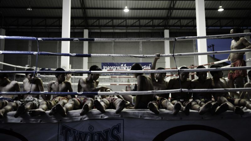BANGKOK, THAILAND - OCTOBER 01: Orphans relax after completing 50 sit-ups at the Phuwana Muay Thai Kickboxing Camp on October 01, 2008 in the Bangyai District, located one hour out of central Bangkok, Thailand. The Phuwana Camp houses children from disadvantaged backgrounds who seek refuge in the martial art of Muay Thai Kickboxing. The children, aged from 7-18, start each day with a 6 km run, train from 4-7 am, attend school from 8-2pm and train again from 3-6pm, seven days a week. Through the camp the students seek guidance, strength, discipline and honour in their training, hoping to gain the respect of their trainers and peers by becoming champion boxers. Despite the sport being viewed as a poor person's sport in Thailand, by winning their competitions the students earn much needed cash prizes, which profit the students and their trainers and allow them to make a life for themselves, supporting themselves financially and also hopefully achieving fame and respect. (Photo by Kristian Dowling/Getty Images)