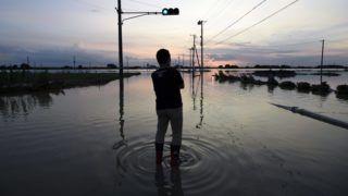 Dzsoszó, 2015. szeptember 11. Egy helyi férfi nézi a naplementét az Ibaraki prefektúrabeli Dzsoszó egyik elöntött utcáján 2015. szeptember 11-én, egy nappal azután, hogy mintegy 80 méteren átszakadt a gát a Kinugava folyón, amely elöntötte a 65 ezer lakosú várost. Japán keleti részén a heves esõzések és áradások következtében három ember életété vesztette, legkevesebb 25-en eltûntek. (MTI/EPA/Franck Robichon)
