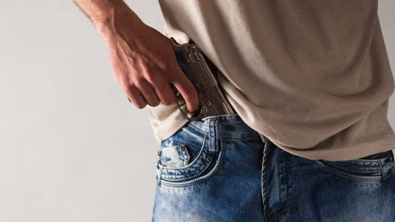 Young man holds glossy metal gun in hand on background of white wall with copy space for your text. Security concept