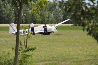 Pusztaszer, 2014. július 2.Rendőrök helyszínelnek a pusztaszeri repülőtéren 2014. július 2-án egy kisrepülőgép mellett, amely manőver közben elsodort egy 18 éves nőt. A fiatal nőt a repülőgép egyik kereke találta fejen, életveszélyes sérüléseket szenvedett.MTI Fotó: Donka Ferenc