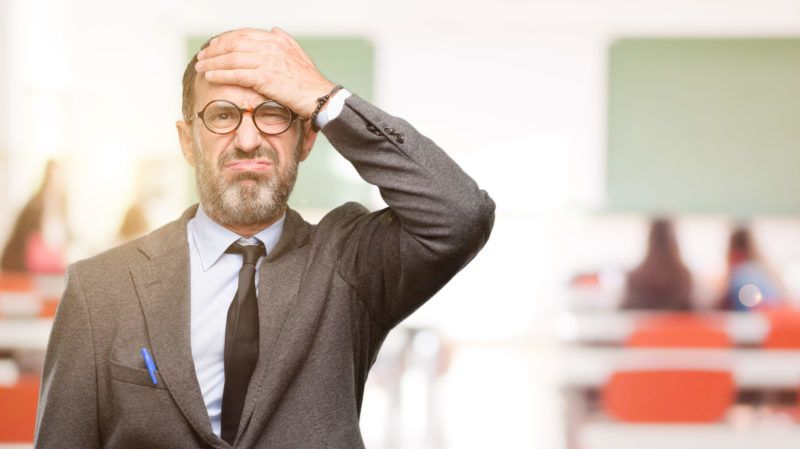Teacher man using glasses terrified and nervous expressing anxiety and panic gesture, overwhelmed at classroom