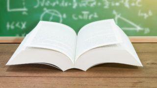 Open textbook on desk on chalkboard.