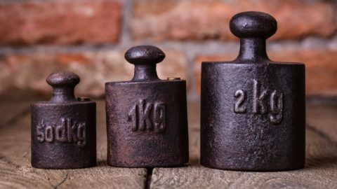 Vintage iron weights in front of an old brick wall.