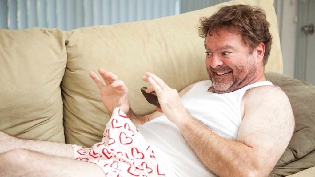 Humorous photo of a man in his underwear, using his cellphone to send a picture of his penis.