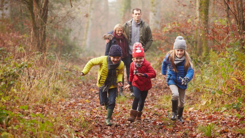 Family Walking Through Winter Woodland Having Fun