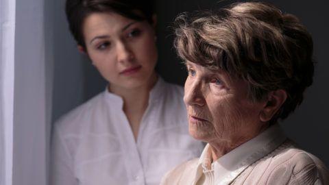 Sad senior woman and good, young carer.