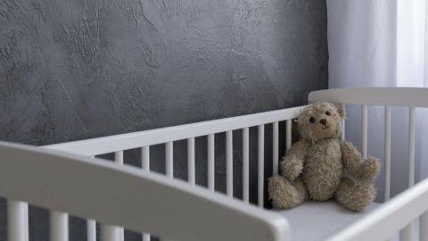 Shot of a teddy bear sitting in a crib