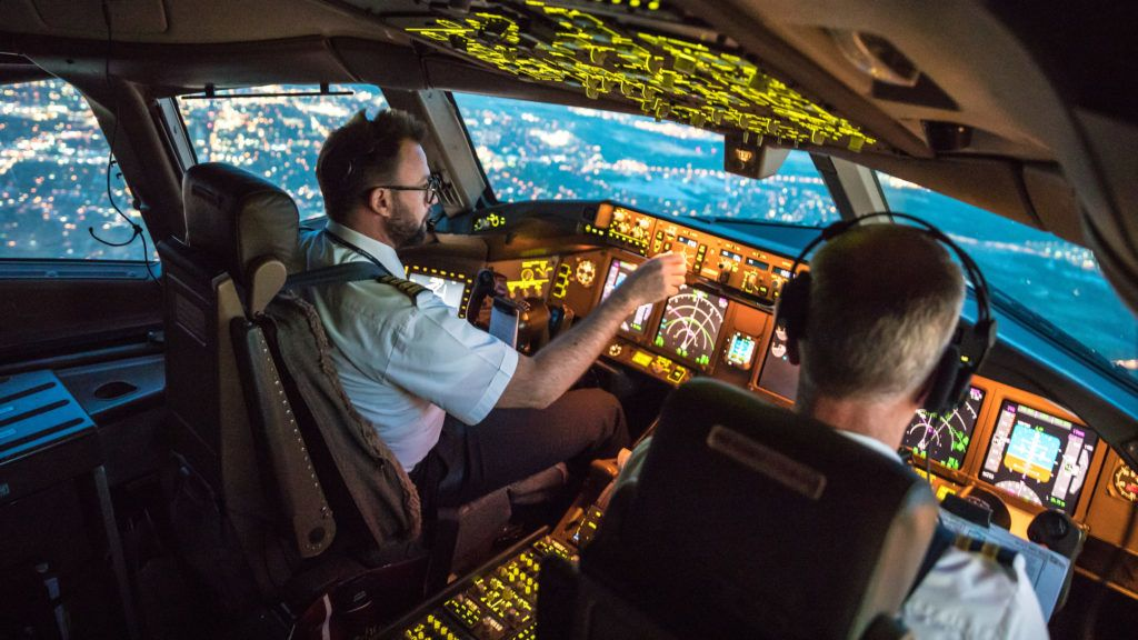 Two pilots at work during departure of Dallas Fort Worth Airport in United States of America. The view from the flight deck with high workload the beginning night through the wind shield
