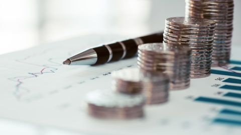 Stack of coins with financial line chart and pen