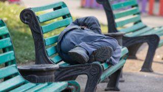 sleeping homeless man on a bench