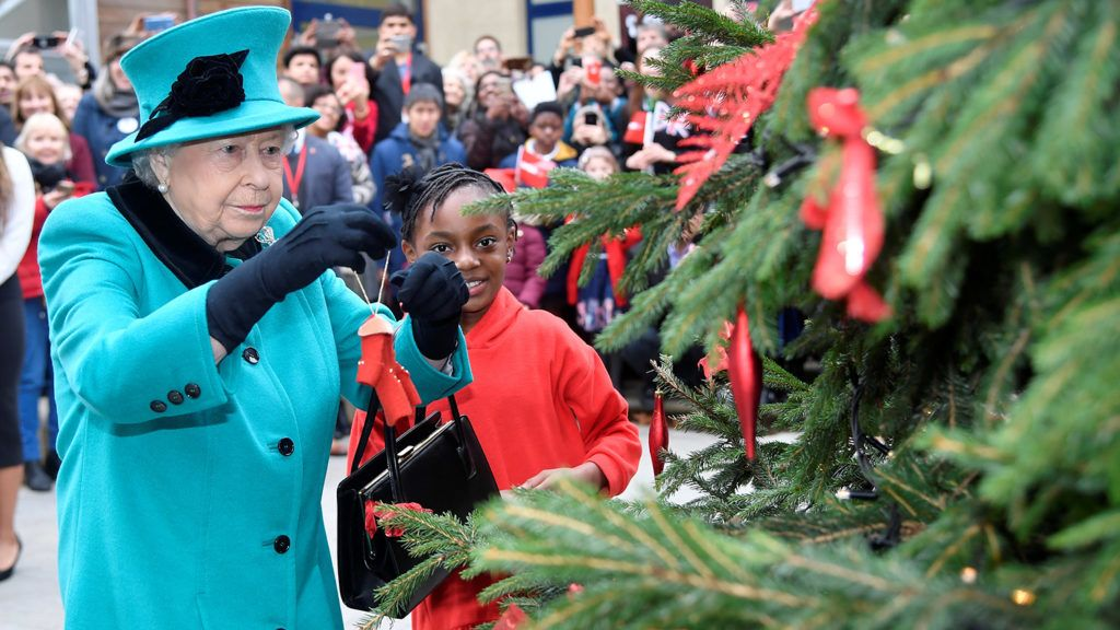 Britain's Queen Elizabeth II (L) and Shylah Gordon attach a bauble to a christmas tree as she visits children's charity Coram in London on December 5, 2018. (Photo by TOBY MELVILLE / POOL / AFP)