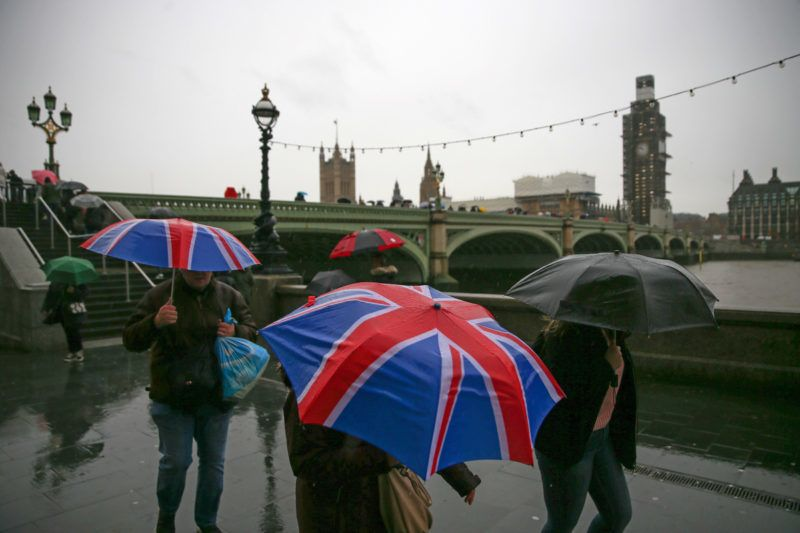 Pedestrians shelter from the rain beneath Union flag-themed umbrellas as they walk along the south bank of the River Thames, near the Houses of Parliament in central London, on December 7, 2018. - British MPs will hold a crucial vote on December 11 to approve or reject the Brexit deal agreed by Prime Minister Theresa May an EU leaders. (Photo by Daniel LEAL-OLIVAS / AFP)
