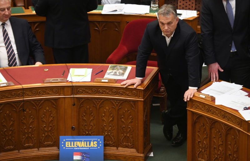"""Hungarian Prime Minister Viktor Orban stands next to a placard reading """"'Resistance, demonstrations"""" displayed by oppositon parties in front of his sitting place during a parliament session on December 12, 2018 in Budapest. - Rare scenes of chaos gripped the Hungarian parliament as it passed changes to the labour code proposed by Orban's party that critics have dubbed a """"slave law"""". The bill loosens labour rules by hiking the maximum annual overtime hours that employers can demand from 250 to 400 hours. (Photo by ATTILA KISBENEDEK / AFP)"""