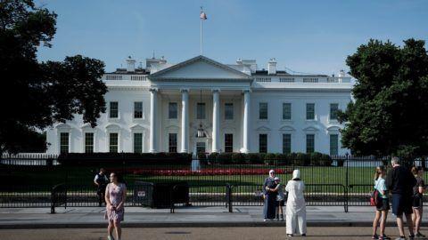 People walk on Pennsylvania Avenue outside the White House on June 18, 2018 in Washington, DC. (Photo by Brendan Smialowski / AFP)