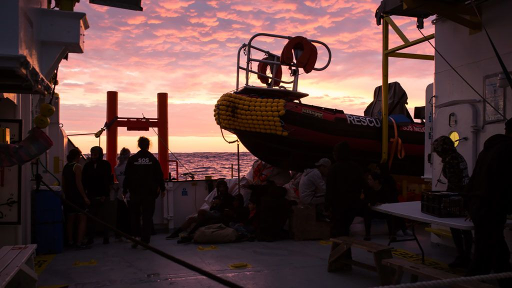 """A handout photo released on September 29, 2018 by SOS Mediterranee shows migrants and a rescuer on September 28 aboard the Aquarius rescue ship run by non-governmental organisations (NGO) """"SOS Mediterranee"""" and """"Medecins Sans Frontieres"""" (Doctors without Borders) in the search and rescue zone off the coast of Libya, in the Mediterranean Sea. (Photo by Maud VEITH / SOS MEDITERRANEE / AFP) / RESTRICTED TO EDITORIAL USE - MANDATORY CREDIT """"AFP PHOTO / SOS MEDITERRANEE / Maud VEITH"""" - NO MARKETING NO ADVERTISING CAMPAIGNS - DISTRIBUTED AS A SERVICE TO CLIENTS"""