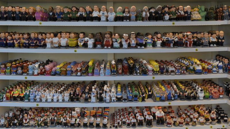 """Picture shows Catalan typical ceramic figurines, called """"caganers"""" (poopies), displayed in Torroella de Montgri on November 6, 2018. - Statuettes of well-known people defecating are a strong Christmas tradition in Catalonia, dating back to the 18th century as Catalans hide 'caganers' in Christmas Nativity scenes and invite friends to find them. (Photo by LLUIS GENE / AFP)"""