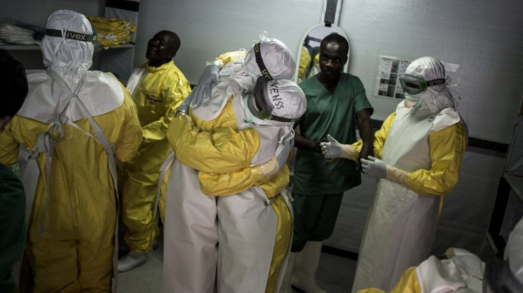 Health workers embrace whilst putting on their personal protective equipment (PPE) before heading into the red zone at a newly build MSF (Doctors Without Borders) supported ebola treatment centre (ETC) on November 7, 2018 in Bunia, Democratic Republic of the Congo. - The death toll from an Ebola outbreak in eastern Democratic Republic of Congo has risen to more than 200, the health ministry said on November 10, 2018. (Photo by John WESSELS / AFP)